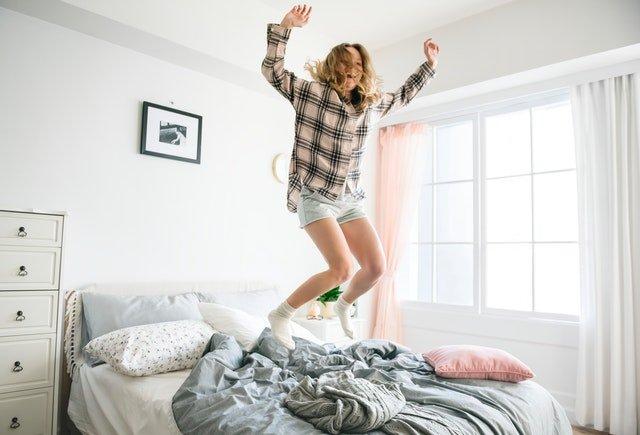žena skákající na rozestlané posteli